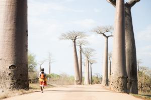 PRIORI Reisen Madagaskar: Madagassische Frau mit Kind läuft durch die Baobab Allee